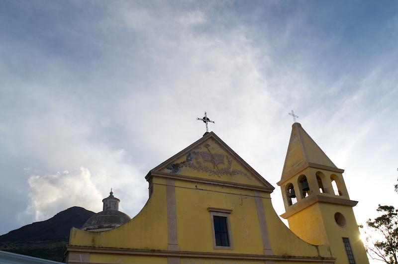 Kirche mit dem rauchenden Stromboli dahinter