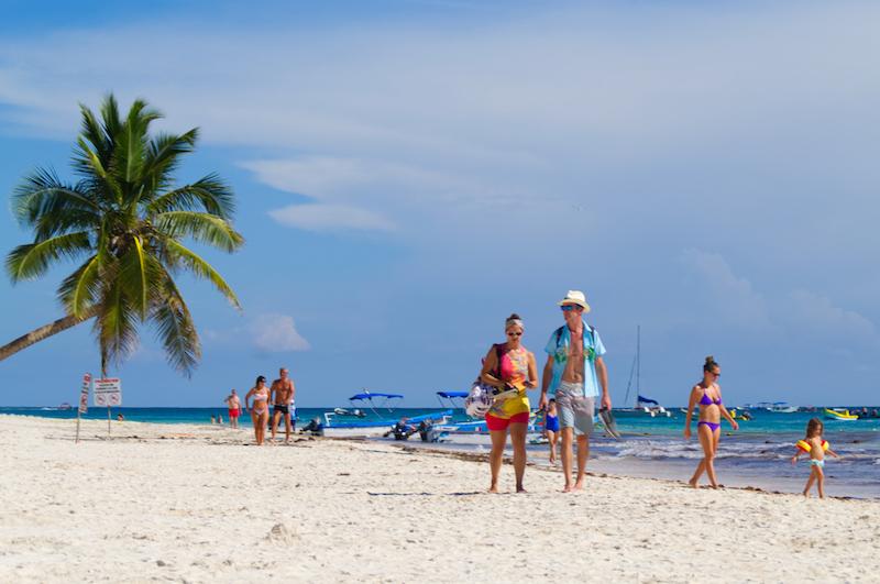 Touristen schlendern über den goldenen Strand von Tulum
