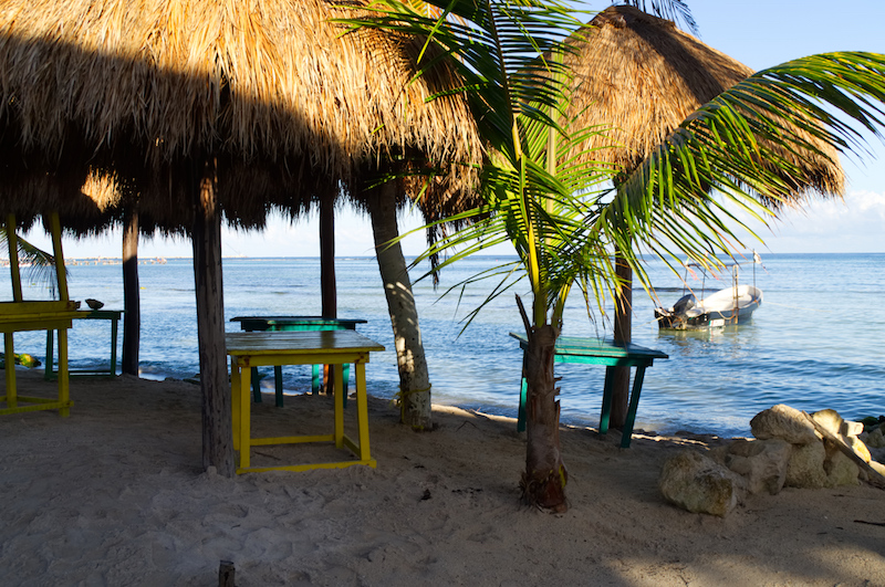 Eine kleine Strandbar mit bunten Tischen in Mahahual