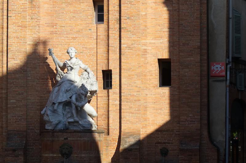 Denkmal und Pixelkunst vor roter Mauer