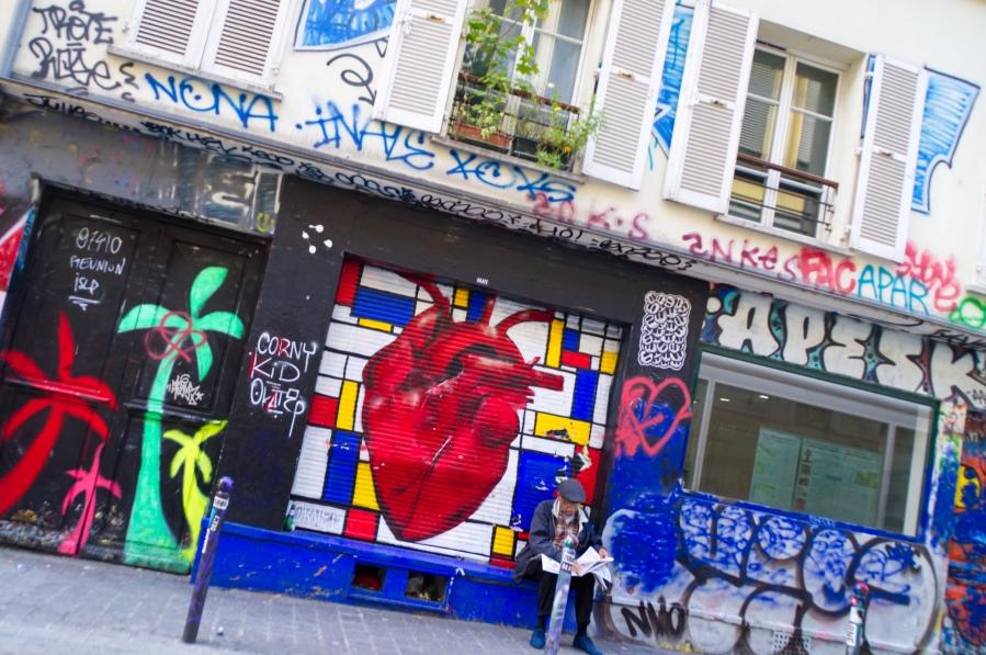 Ein zeitungslesender Mann vor Streetart in Paris