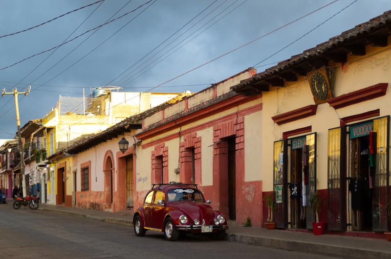 Roter VW Käfer in einer Straße voller Cafés