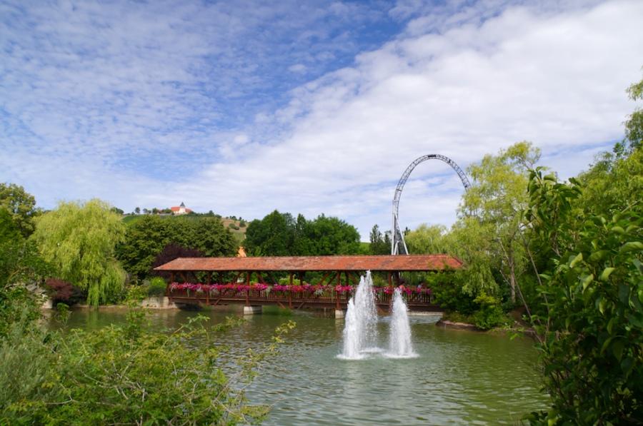 Ein See mit Springbrunnen, Karacho und Weinberge im Hintergrund