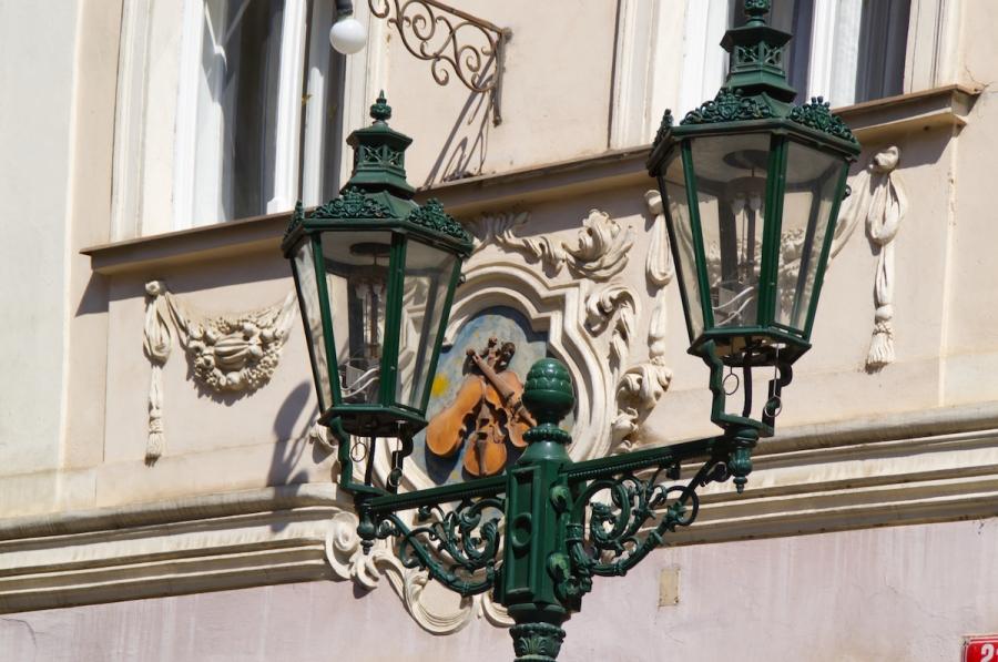 Straßenlaterne und dahinter ein Wappen aus drei Violinen