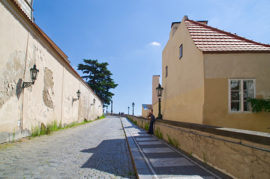 Ein einsamer Straßenmusikant steht auf dem Weg zur Prager Burg