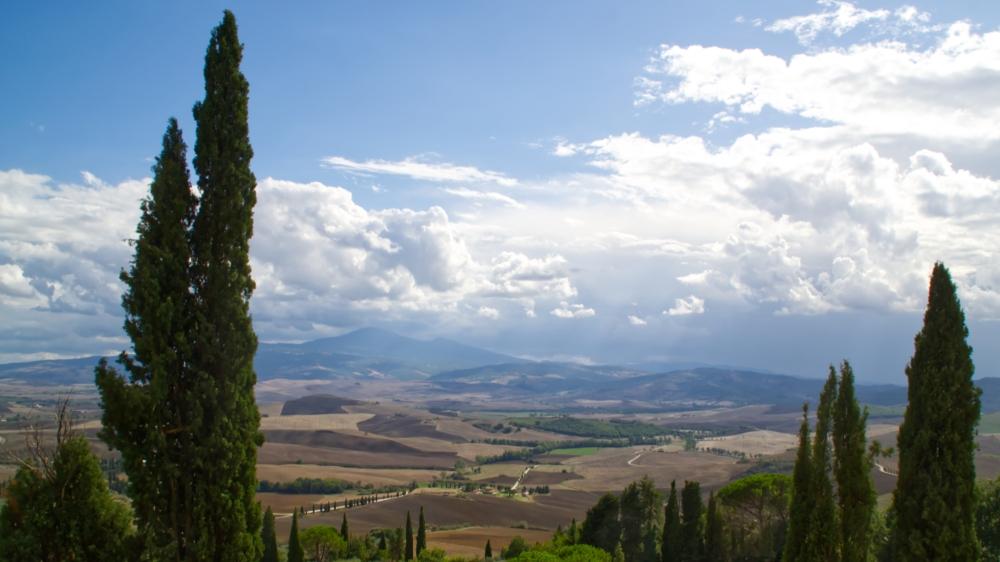 Die liebliche Hügellandschaft der Toskana mit Zypressen, Feldern und Wolken